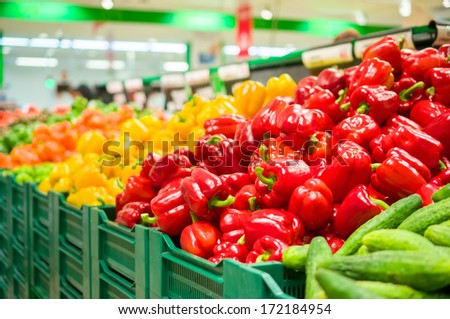 Bunch of red, yellow and orange paprika peppers on boxes in supermarket - stock photo