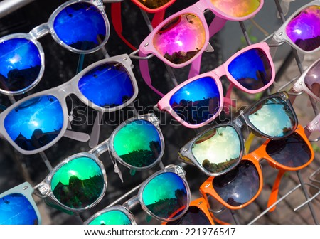 bunch of retro style sunglasses on a rack in front of a store