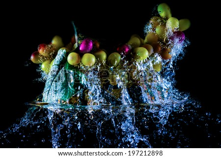 bunch of ripe grapes in water on a black background - stock photo