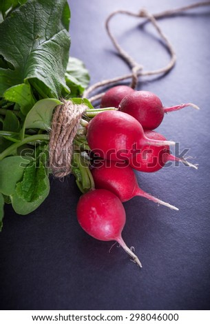 Bunch of ripe red radish on black background, selective focus and shallow depth - stock photo