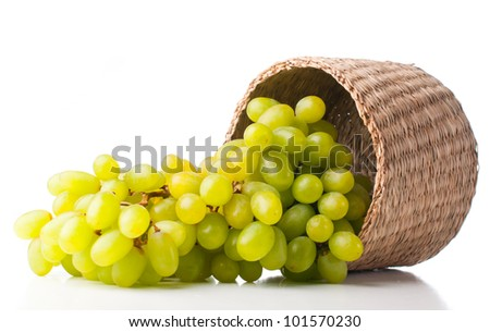 Bunch of ripe white grapes in a wicker basket on a white background - stock photo