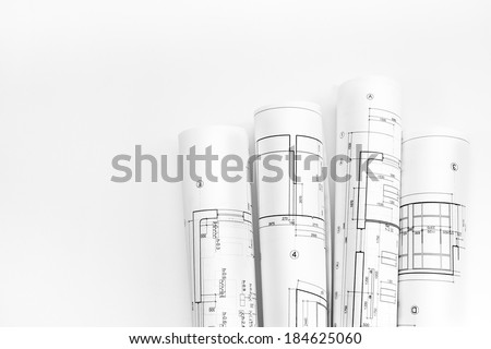 Bunch of rolled up building plans and technical drawings - stock photo
