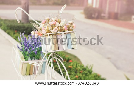 Bunch of rose flowers in white bicycle's basket with sunlight