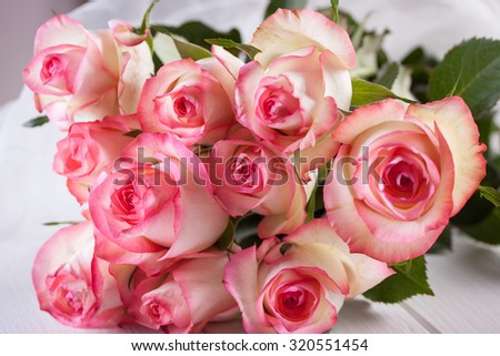 Bunch of roses on white wooden background - stock photo