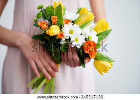 Bunch of roses, tulips and chrysanthemums held by female