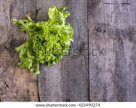 bunch of salad on old weathered wooden surface - stock photo