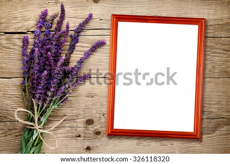 Bunch of salvia and empty photo frame on wooden background - stock photo