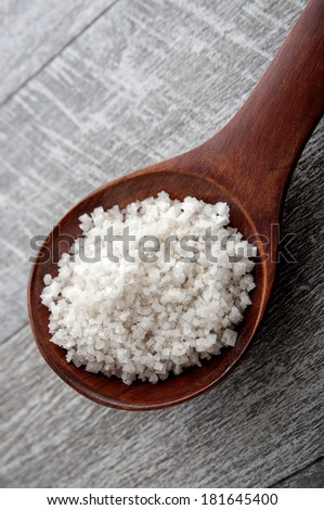Bunch of sea salt on a wooden spoon, close up