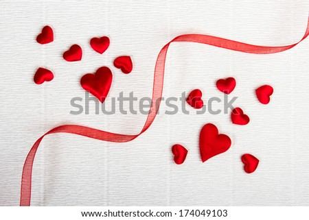 Bunch of small fabric hearts divided by a red ribbon. Valentine
