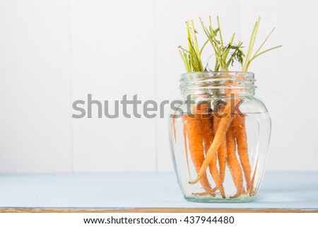 Bunch of small fresh garden carrots in glass bottle of water on bright white and blue wooden background, copy space - stock photo