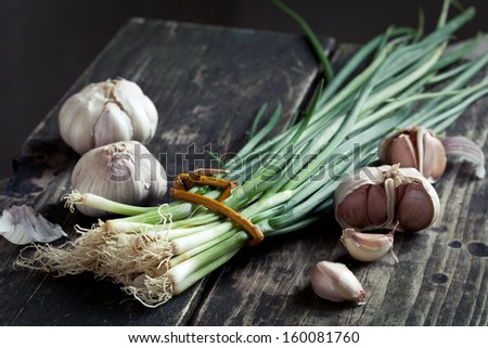 bunch of spring onions and garlic on wood - stock photo