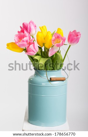 Bunch of spring tulips flowers in metal pot isolated on white - stock photo
