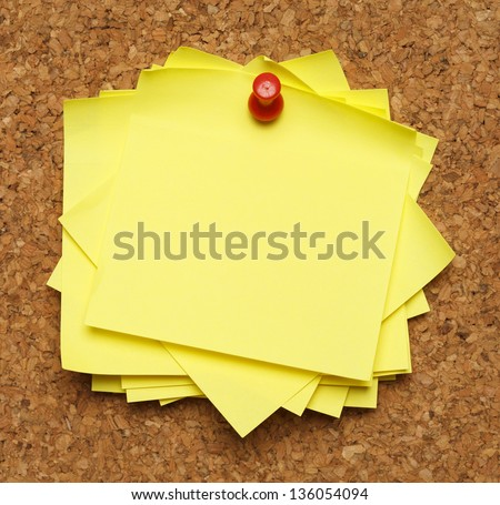 Bunch of sticky notes tacked to cork board. - stock photo