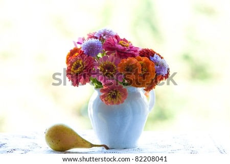 Bunch of summer garden flowers into a white porcelain vase and  a pear - stock photo