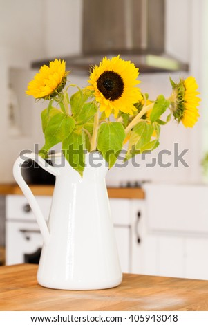 Bunch of sunflowers in vase in the kitchen - stock photo