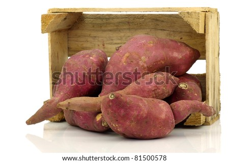 Bunch of sweet potatoes in a wooden crate on a white background - stock photo