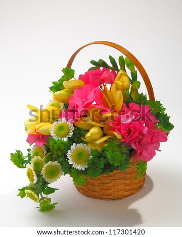 bunch of the flowers arranged in the basket isolated in gray - stock photo