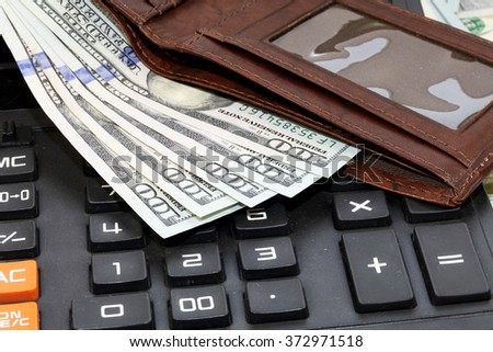bunch of the new one hundred dollar bills wallet and a calculator - stock photo
