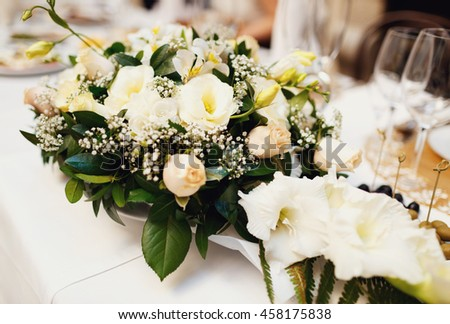 Bunch of the white flowers on the wedding table - stock photo