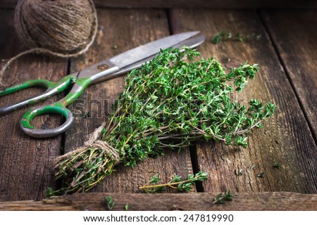 bunch of thyme on old wooden board - stock photo