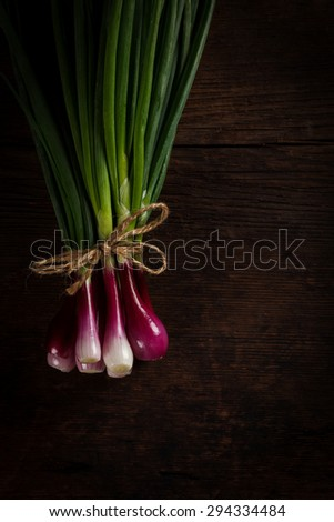 Bunch of tied onions on rustic wooden table