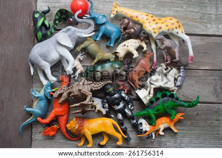 Bunch of toys table. Animals, dinosaurs & soldier bunch of toys laying on dirty old wooden table upper view. - stock photo