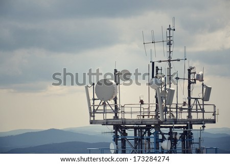 Bunch of transmitters and aerials on the telecommunication tower. - stock photo