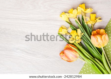 Bunch of tulips and narcissus on cotton napkin on wood. Space for your text - stock photo