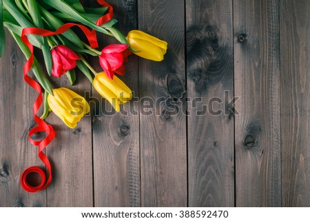 Bunch of tulips on dark wooden table with ribbon. Copyspace - stock photo