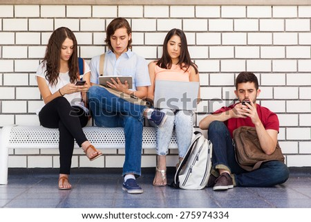 Bunch of university students sitting in a bench in the school hallway and using all kinds of technology - stock photo