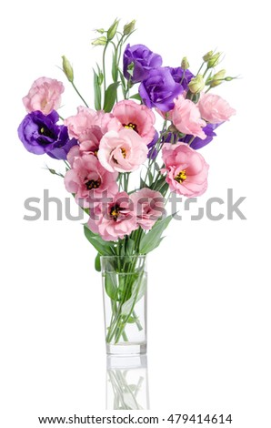 bunch of violet, white and pink eustoma flowers in glass vase isolated on white