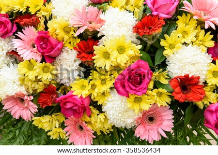 Bunch of vivid flowers, flower bouquets including light purplish red roses, white chrysanthemums, pinke gerberas, and red marguerite daisies.