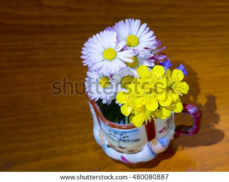 Bunch of white and yellow small flowers in a cup