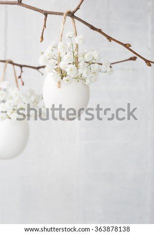Bunch of white baby's breath flowers (gypsophila) in eggs shell on the white wooden plank. Shallow depth of field, focus on near flowers. Easter decor - stock photo