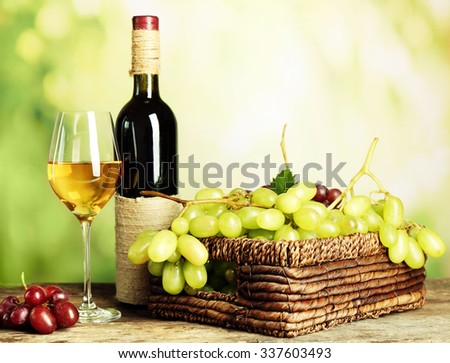 Bunch of white grape in basket with wine bottle on wooden table