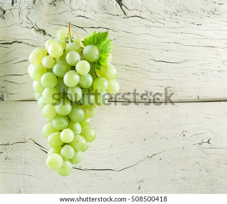 Bunch of white grapes. Old wood on the background.