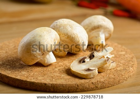Bunch of white mushrooms on the wooden background - stock photo
