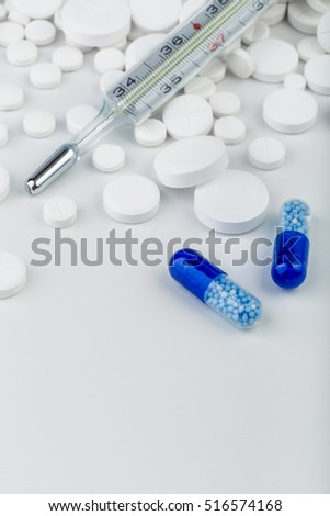 Bunch of white tablets with blue pills and thermometer. Scattered pills.Selective focus.