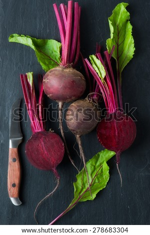 Bunch of whole beetroots farm fresh on dark background - stock photo