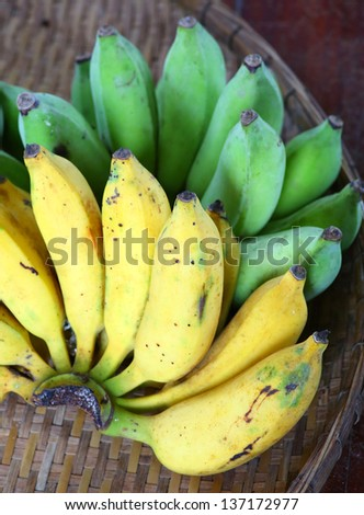 Bunch of yellow and green banana on bamboo weave