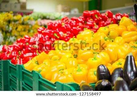 Bunch of yellow and red paprika peppers on boxes in supermarket