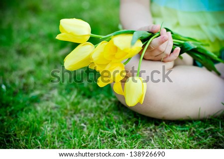 Bunch of yellow tulips in child's hands outdoors - stock photo