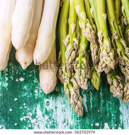 Bunch of young green and white asparagus with sea salt over green wooden table. Square image  - stock photo