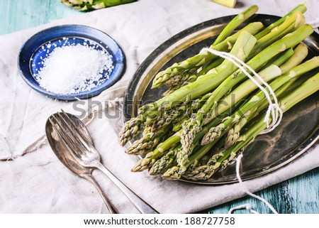 Bunch of young green asparagus on vintage tray served with ceramic plate of sea salt and silver cutlery over green wooden table. - stock photo