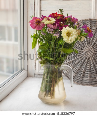 Bunch of zinnias at the window in a glass jar