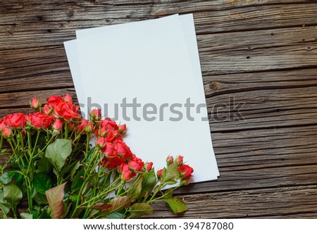 Bunch or fresh red roses for a Valentines sweetheart arranged in the corner of sheets of blank white notepaper for your greeting to a loved one - stock photo