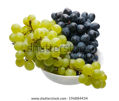 Bunches of black and green grapes in a white cup on a white background, isolated - stock photo