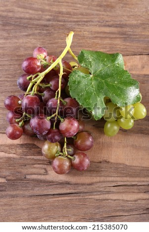 Bunches of different kinds of grapes on wooden background - stock photo