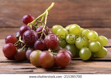 Bunches of different kinds of grapes on wooden table on wooden wall background - stock photo
