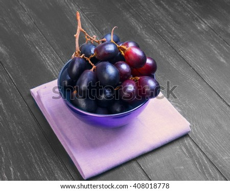 Bunches of grapes Crimson large in purple mask on a napkin on a black wooden background in rustic style - stock photo